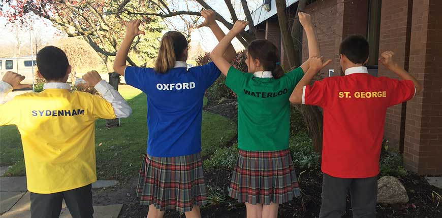 Students wearing house shirts with the house names on the back
